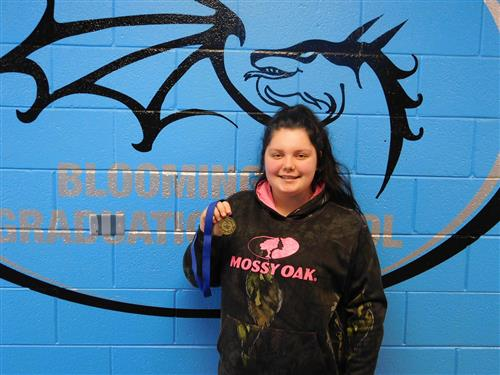 "A pale, femme student in a camo and pink sweatshirt that says ""Mossy Oak"", holding up her medal for student of the month."