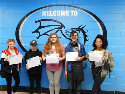 Five students stand in front of the BGS logo holding their perfect attendance certificates.
