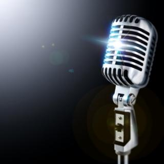 Silver microphone on a black background with light flares in the upper left corner and the center of the microphone.