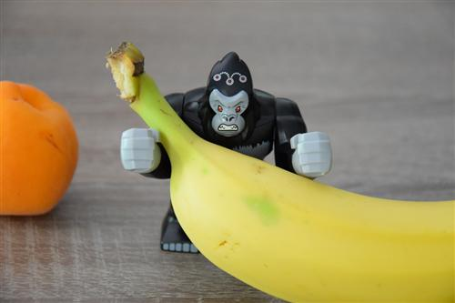 A toy, angry-looking gorilla propped behind the stem of a banana with an apricot off to the left side.